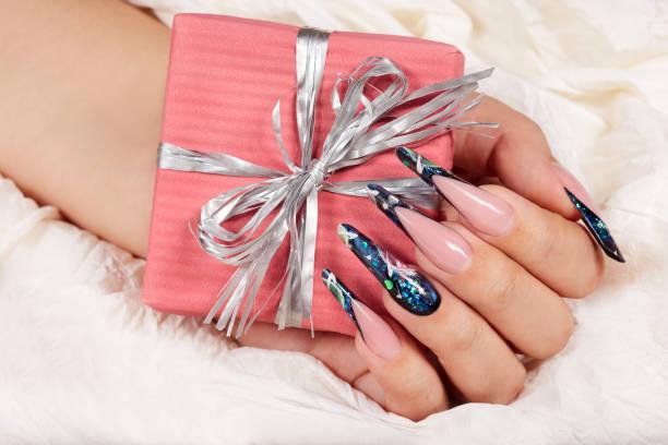 hand mit langen künstlichen gepflegten nägel french hält eine geschenkbox mit schleife - nageldesign weihnachten stock-fotos und bilder