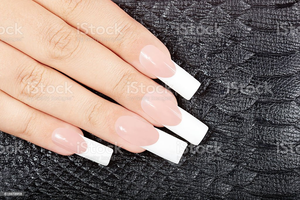Hand with long artificial french manicured nails on black leather...