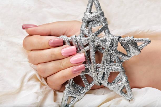 hand mit langen künstlichen rosa manikürten nägel mit einem silver star - nageldesign weihnachten stock-fotos und bilder