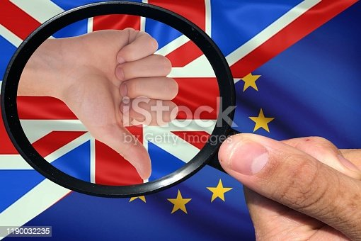 Hand with magnifying glass in search of the Brexit solution