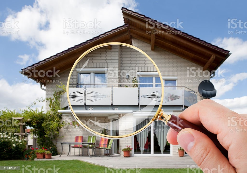Hand With Magnifying Glass Over House stock photo
