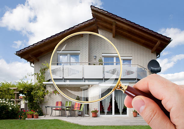 hand with magnifying glass over house - examining stock photos and pictures