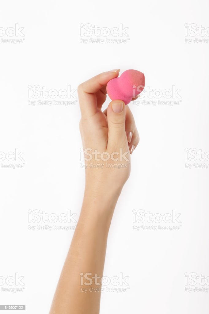 Hand with make up make up sponge isolated on white stock photo