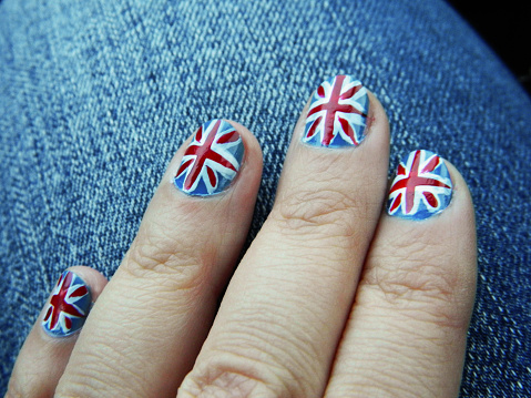 Hand with manicure in British Flag stile. Woman's hands with blue manicure.