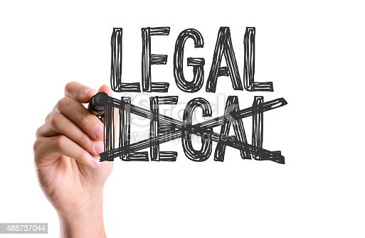 Hand with marker writing the word Legal/Ilegal