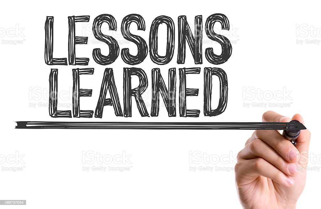 hand with marker writing the word lessons learned stock