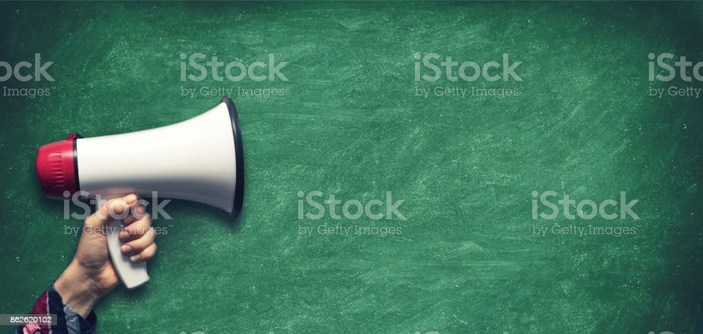 hand with megaphone on blank green chalkboard background stock photo