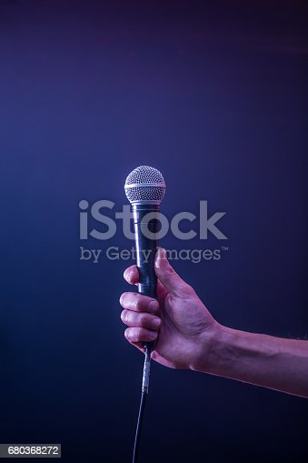 istock hand with microphone on a black background, the music concept, beautiful lighting on the stage 680368272