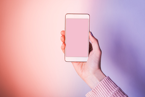 istock Hand with mobile phone screen on pink and purple 1137746629