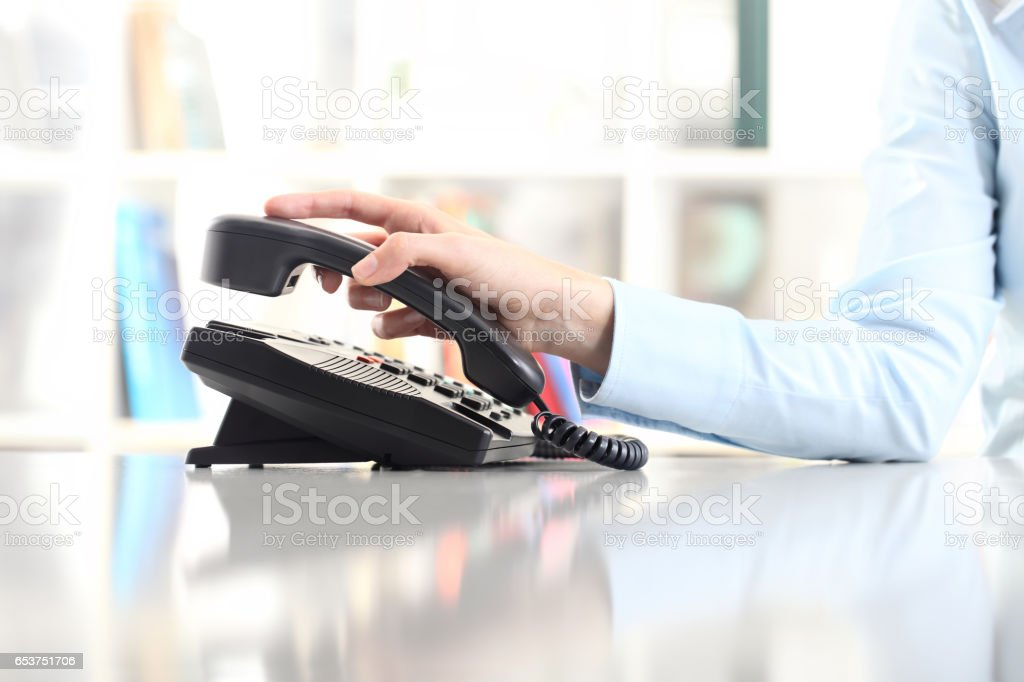 hand with office phone on desk'n stock photo