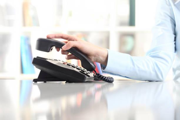 """hand with office phone on desk""""n - cornetta telefono foto e immagini stock"""