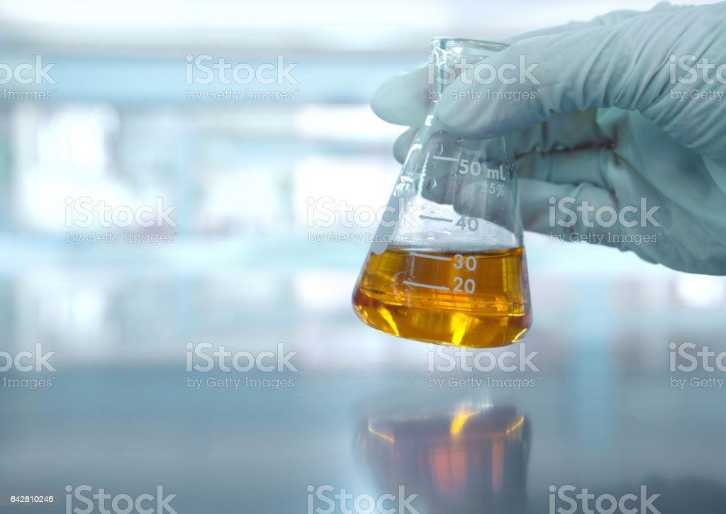 hand with orange solution in scientist hand with science laboratory stock photo