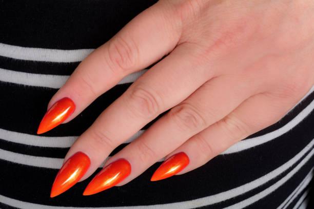 hand mit orange stiletto maniküre auf gestreiften stoff - nails stiletto stock-fotos und bilder