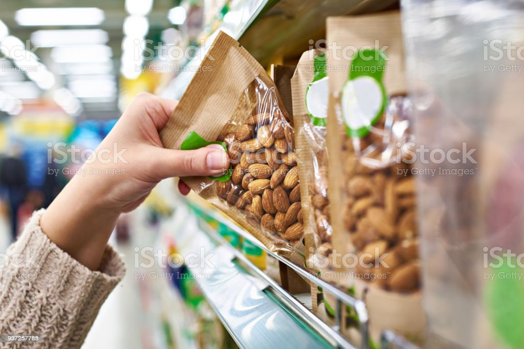 Hand with packaging of almond nuts in store stock photo
