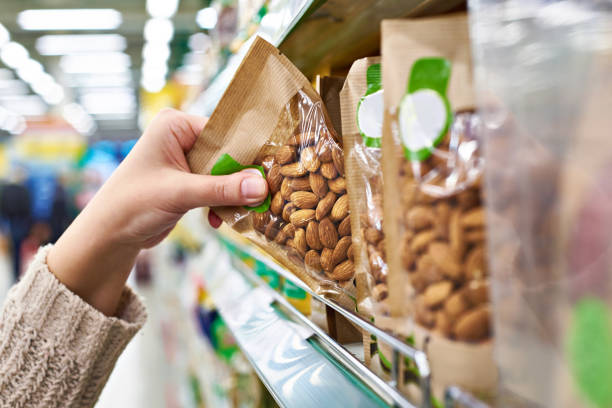 hand with packaging of almond nuts in store - packaging foto e immagini stock
