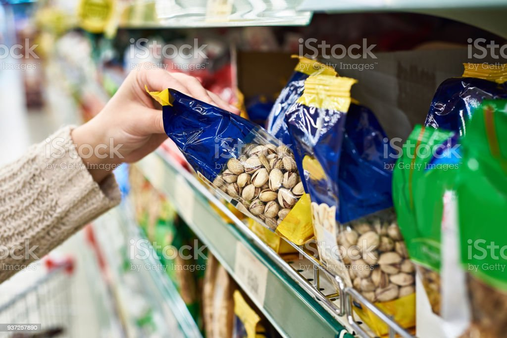 Hand with packing of salted pistachios in store stock photo