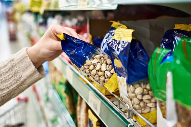 hand with packing of salted pistachios in store - nut food stock photos and pictures