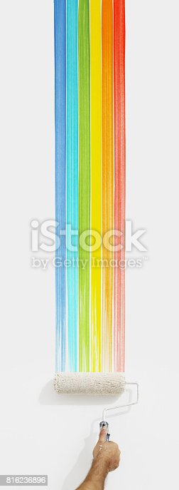 istock hand with paint roller painting color rainbow, close up  isolated on blank white wall background 816236896