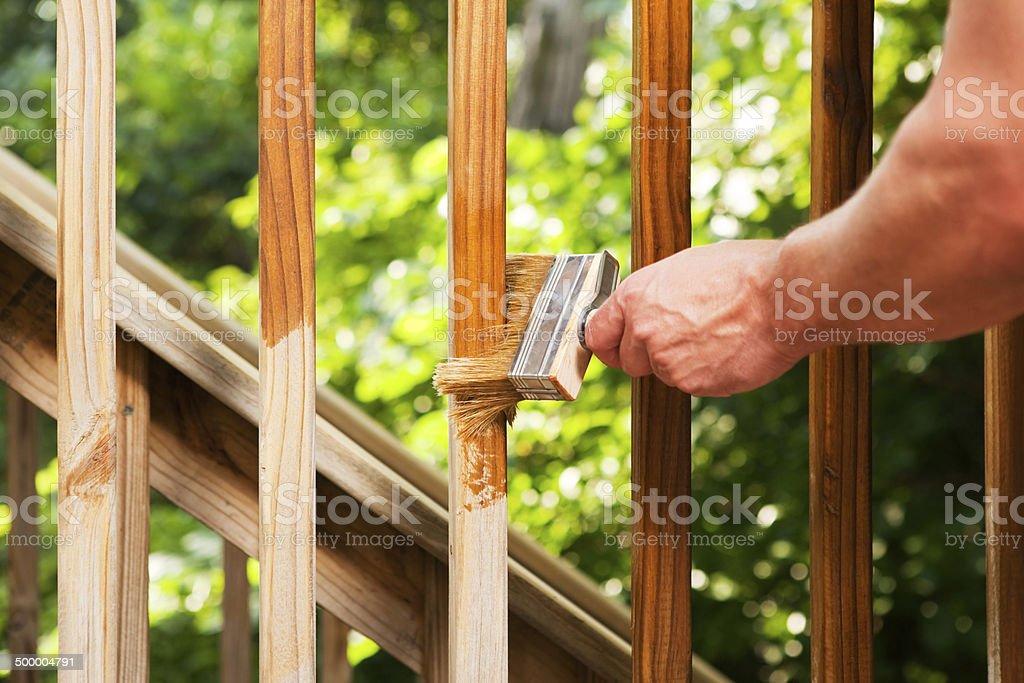 Hand with Paintbrush Staining Wood Deck Railing stock photo