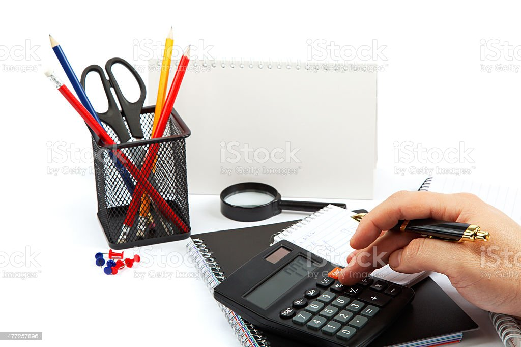 Hand with pen and calculator, notepad and office supplies. stock photo