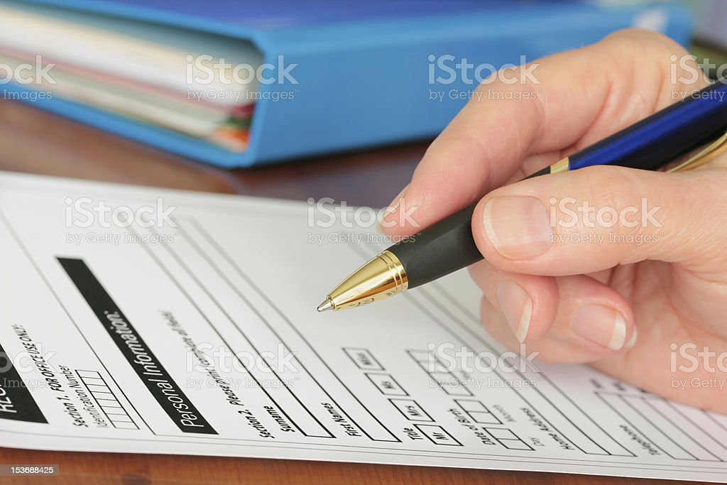 Hand with Pen Completing Personal Information on Form stock photo