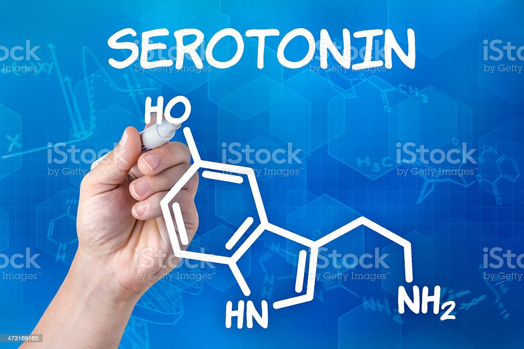 hand with pen drawing the chemical formula of serotonin stock photo