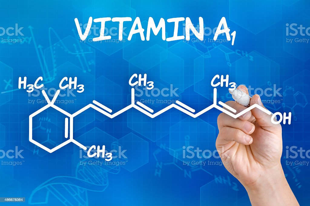 Hand with pen drawing the chemical formula of Vitamin A stock photo