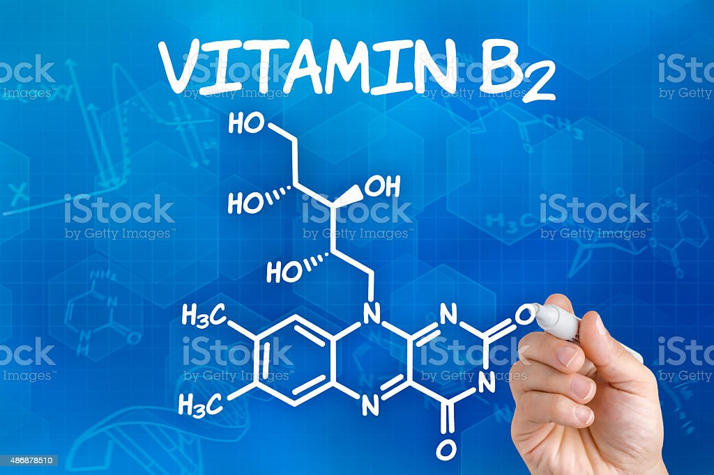 Hand with pen drawing the chemical formula of  Vitamin B2 stock photo