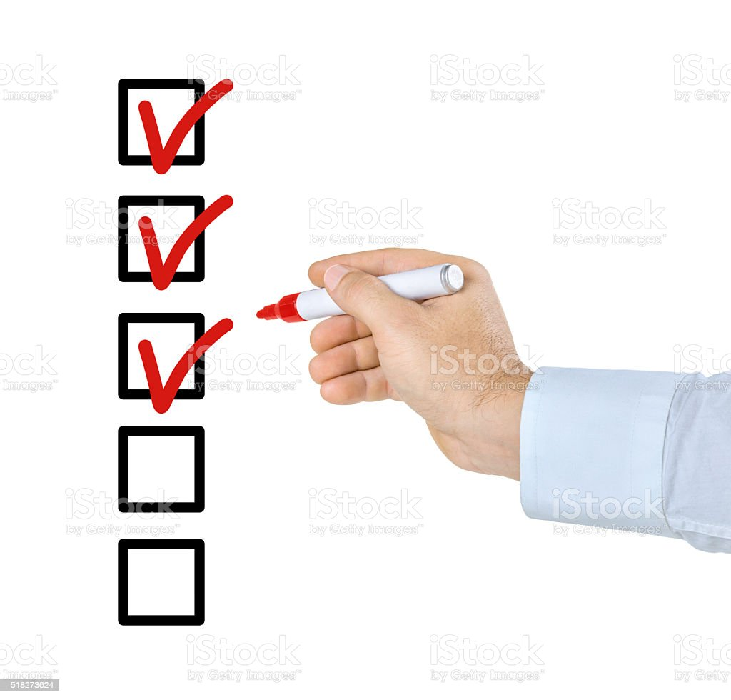 Hand with pen filling out a checklist stock photo