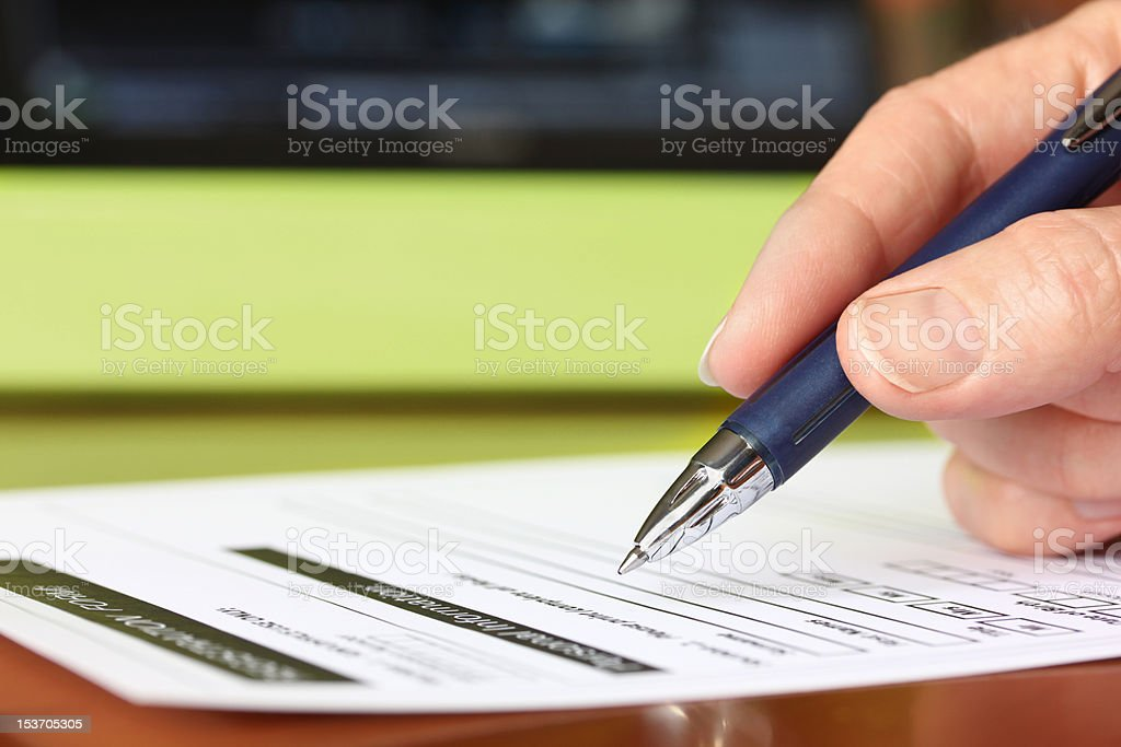 Hand with Pen Signing Form by Green Folder royalty-free stock photo