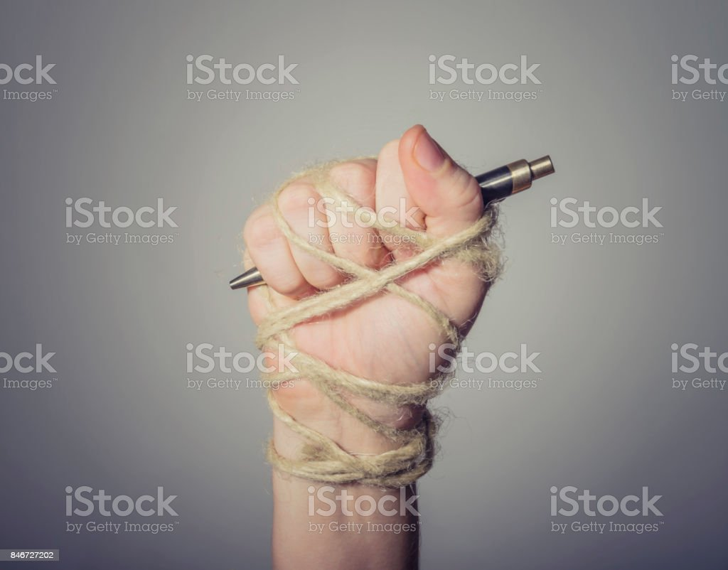 Hand with pen tied with rope stock photo