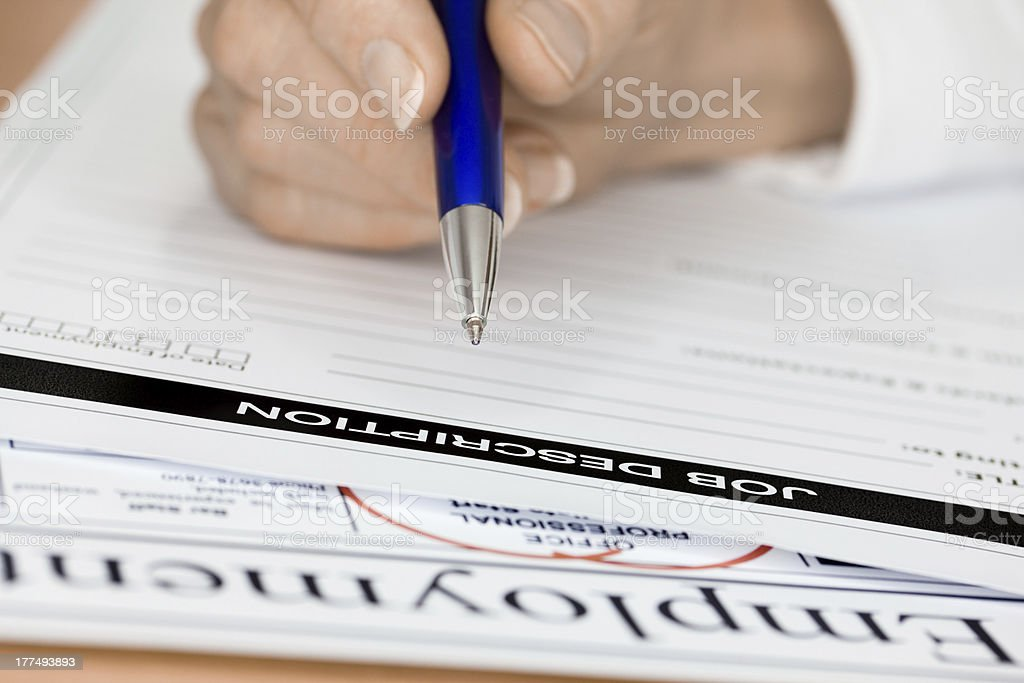 Hand with Pen Writing a Job Description for Employee stock photo