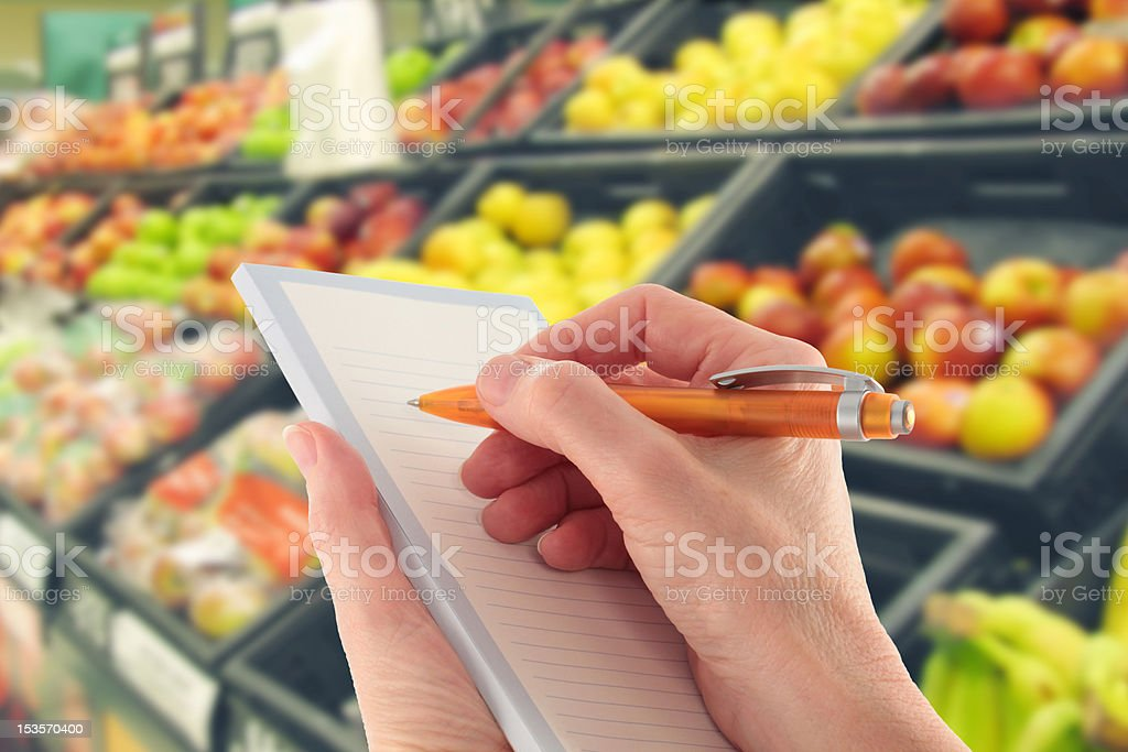 Hand with Pen Writing a Shopping List by Supermarket Fruit royalty-free stock photo