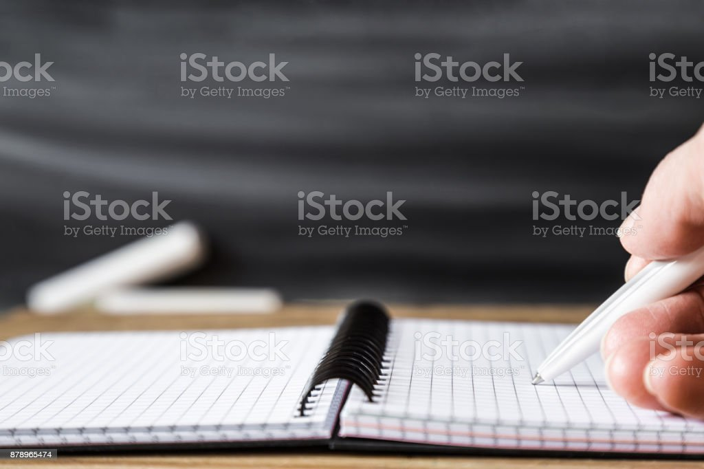 Hand with pen writing in notepad on the table at the blackboard in classroom. Education concept. Empty place for a text. stock photo