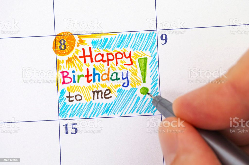 Hand with pen writing reminder Happy Birthday to me stock photo