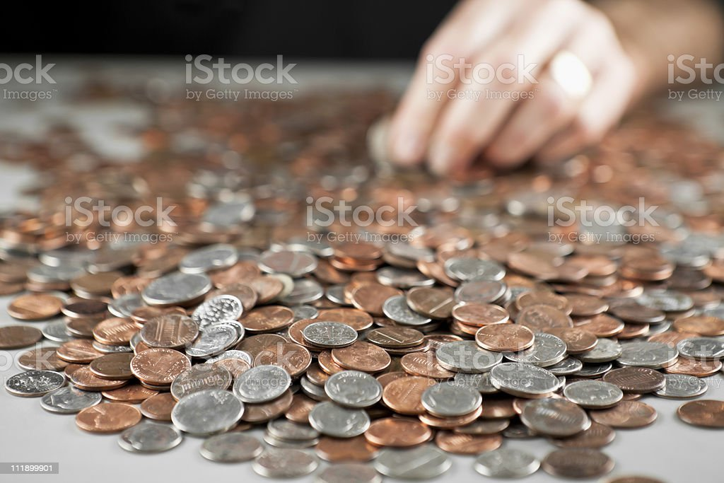 Hand with pile of coins. Counting. stock photo
