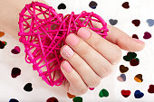 Hand with pink matte manicured nails holding a heart