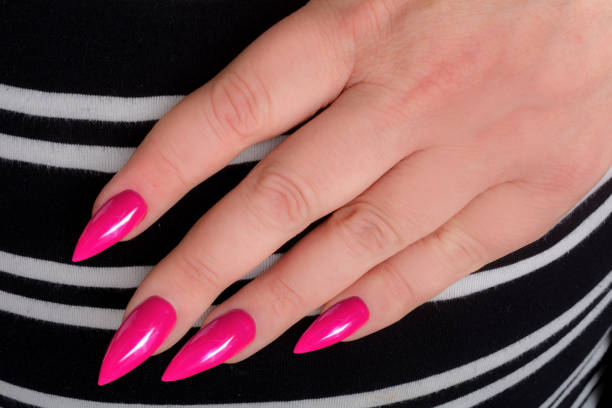 Hand with Pink stiletto manicure on striped fabric Pink stiletto manicure on striped dress pink nail polish stock pictures, royalty-free photos & images