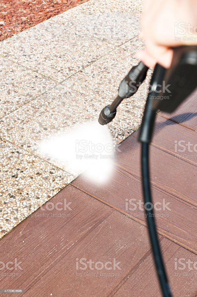 Hand with pressure washer washing different floor surfaces stock photo