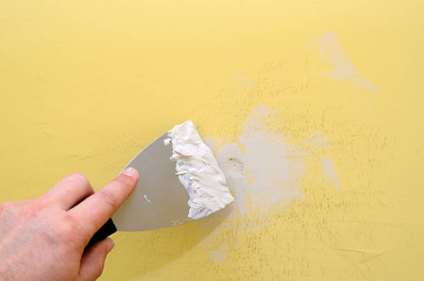 Hand with putty knife repairing damaged wall stock photo