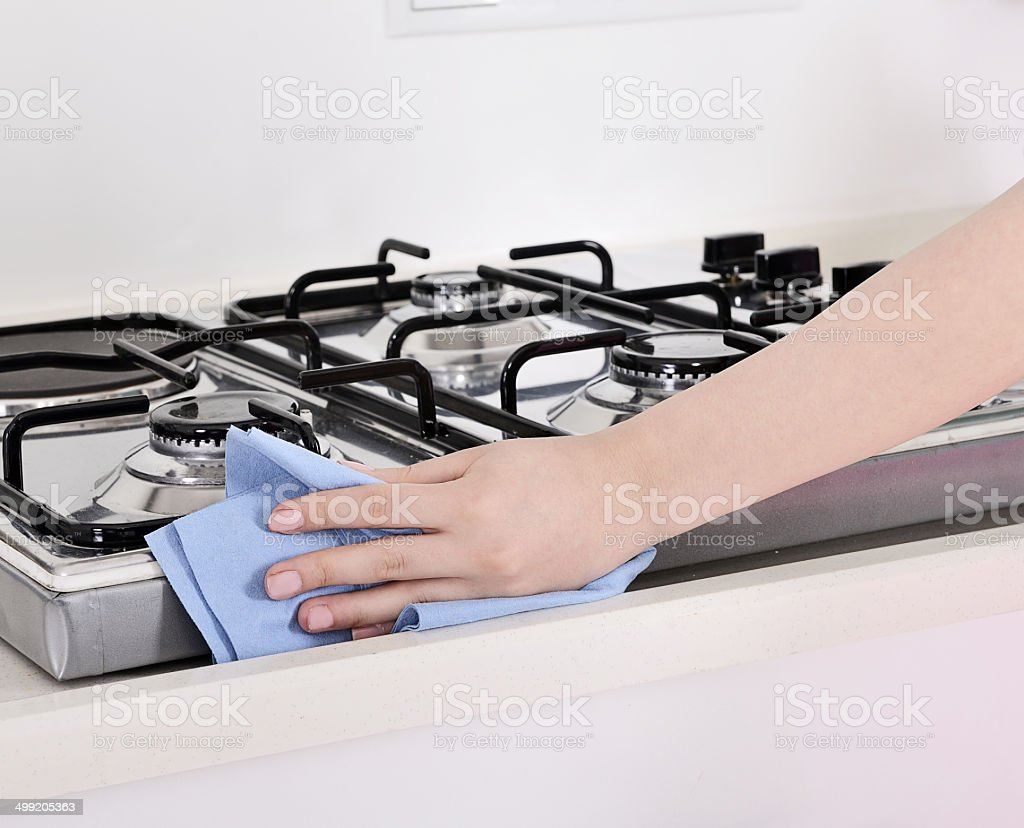 Hand with rag wiping down stainless steel stove top range royalty-free stock photo
