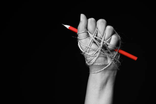hand with red pencil tied with rope, depicting the idea of freedom of the press or freedom of expression on dark background in low key. international human rights day concept. - spingere foto e immagini stock