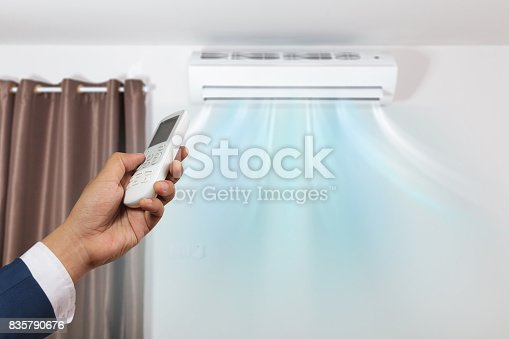 istock Hand with remote control directed and air conditioner 835790676