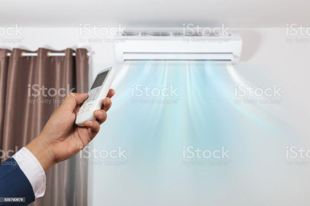 Mano con control remoto dirigido y aire acondicionado - foto de stock
