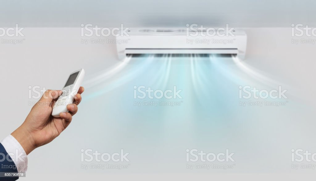 Hand with remote control directed and air conditioner stock photo