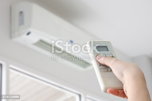 istock Hand with remote control directed on air conditioner 519225686