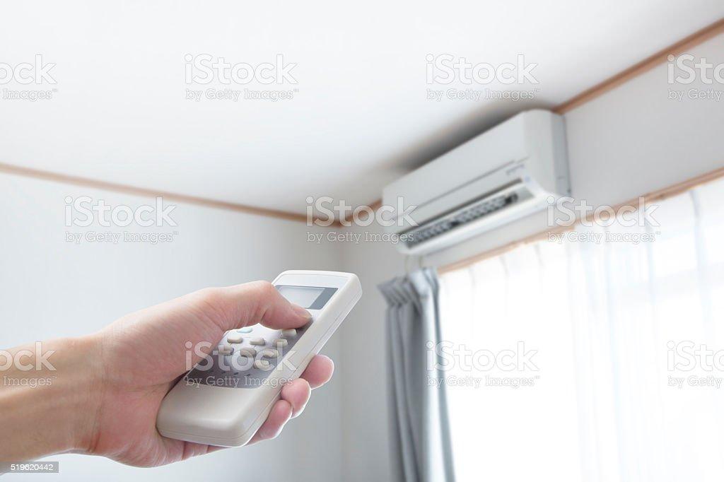 Mano con control remoto s'indica en el acondicionador - foto de stock
