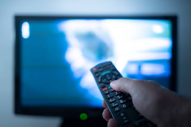 Hand with remote control in front of the tv stock photo