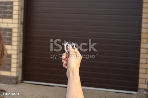 istock Hand with remote control opens automatic sectional garage door 1162915790