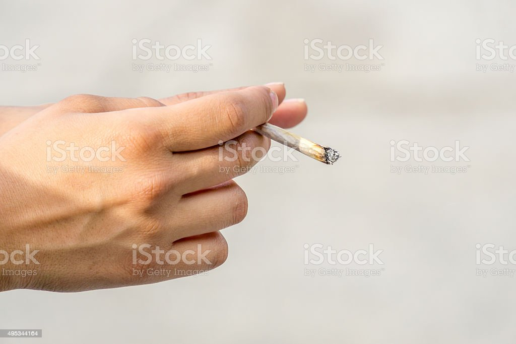 Hand with Rolled Cigarette or Joint stock photo